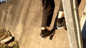 Cropped image of someone climbing up a short concrete wall - only legs are visible.
