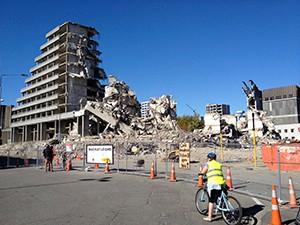 Image of fenced off demolition site in Christchurch with collapsed buildings, post earthquake
