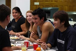 Students sitting at a dining table in an accommodation building.