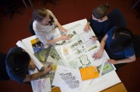 An overhead shot of a group of students studying with urban maps.